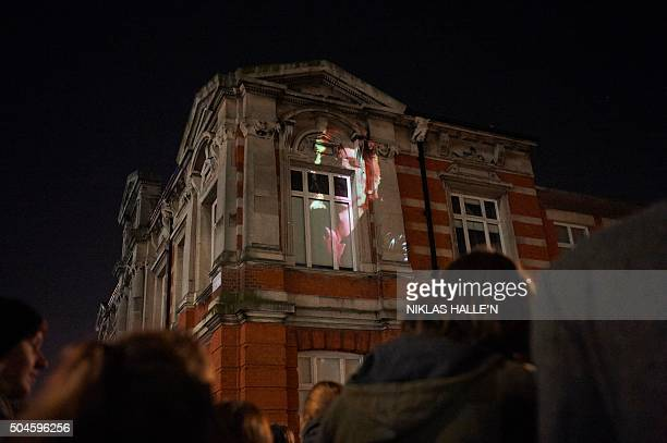An image of David Bowie is projected on Brixton's library as crowds are gathered to pay homage to British singer David Bowie following the...