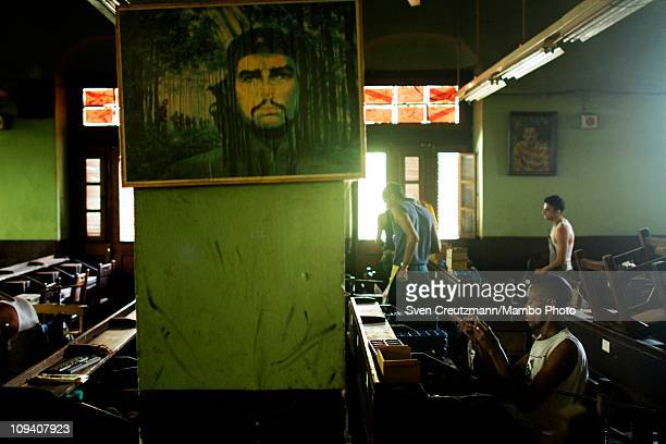 An image of Ernesto Che Guevara hangs on a wall as a worker rolls Cuban cigars in the Partagas cigar factory in Old Havana during the 13th Habanos...