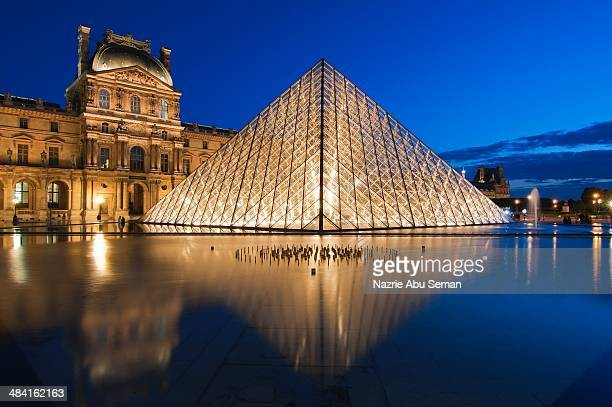 An image of Louvre Museum taken in the blue hour in Paris France
