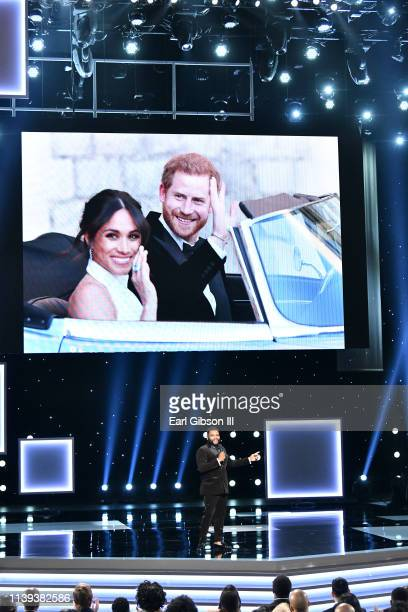 An image of Meghan Duchess of Sussex and Prince Harry Duke of Sussex is projected on a video screen while Anthony Anderson speaks onstage at the 50th...