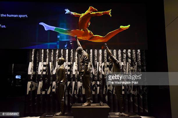 An image of Olympic gymnast Gabby Douglas is projected above a statue depicting USA track and field athletes Tommie Smith C and John Carlos R as they...