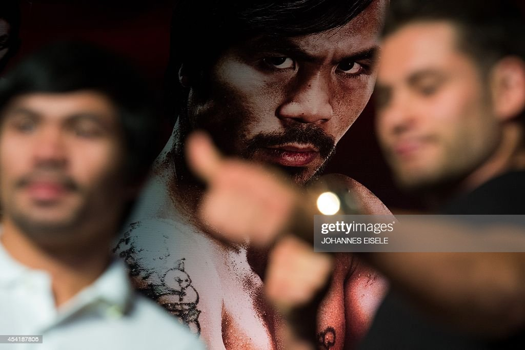 An image of Philippine boxing icon Manny Pacquiao (back C) looks down at Pacquiao (front L) and Chris Algieri (front R) of the US as they pose during a pre-fight press conference in Shanghai on Aug...
