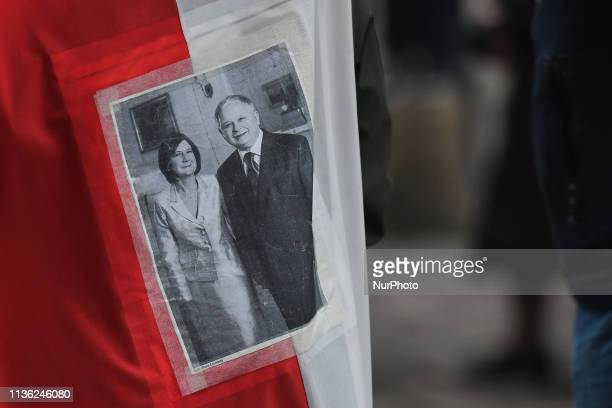 An image of President Lech Kaczynski and his wife Maria Kaczynski seen attached to a Polish flag outside of Katyn Cross monument near Wawel Castle on...