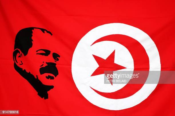 TOPSHOT An image of prominent opposition figure Chokri Belaid is seen printed on a Tunisian flag as mourners gather for a ceremony to mark the fifth...