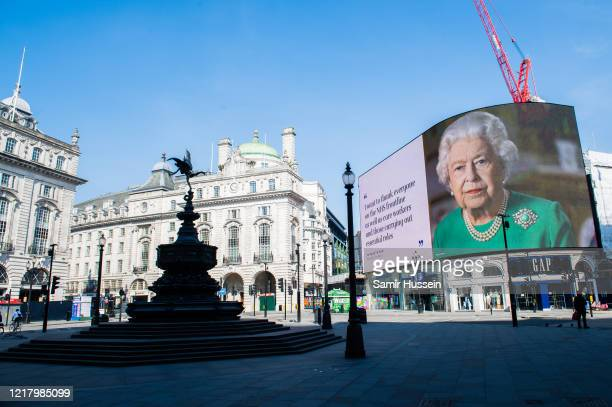 An image of Queen Elizabeth II and quotes from her broadcast to the nation in relation to the coronavirus epidemic are displayed on screens in...