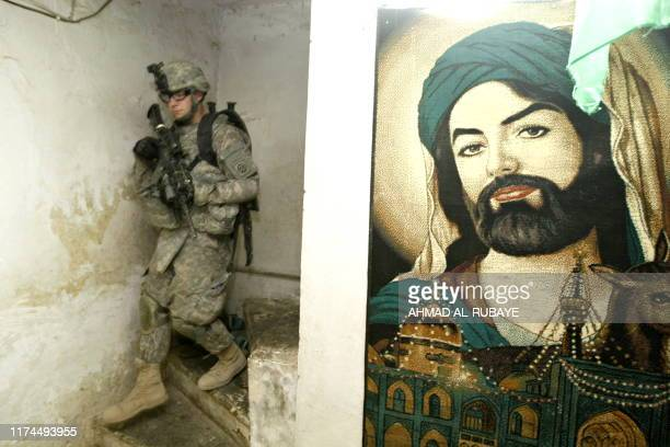 An image of Shiite Muslim Imam Ruda who is buried in Iran hangs on the wall as a US soldier walks down some stairs during a joint patrol with Iraqi...