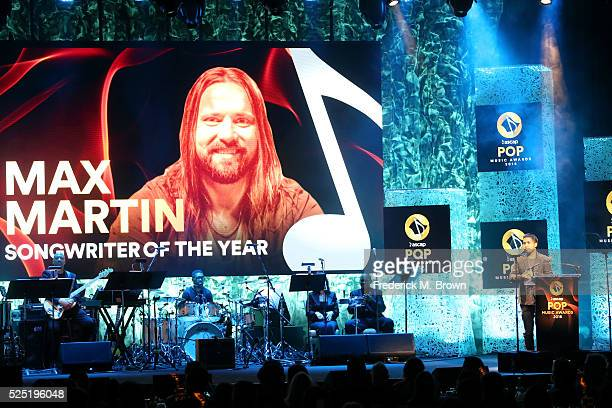 An image of Songwriter Of The Year honoree Max Martin is projected on a screen as songwriter/record producer Savan Kotecha speaks onstage during the...