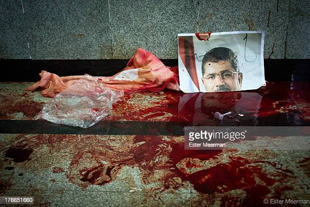An image of the deposed Egyptian president Mohammed Morsi stands in a pool of blood at the makeshift morgue at the Muslim Brotherhood sit-in at Rabaa...
