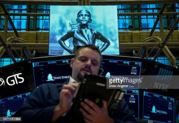 An image of the 'Fearless Girl' statue is displayed on a screen as traders work ahead of the opening bell on the floor of the New York Stock Exchange...