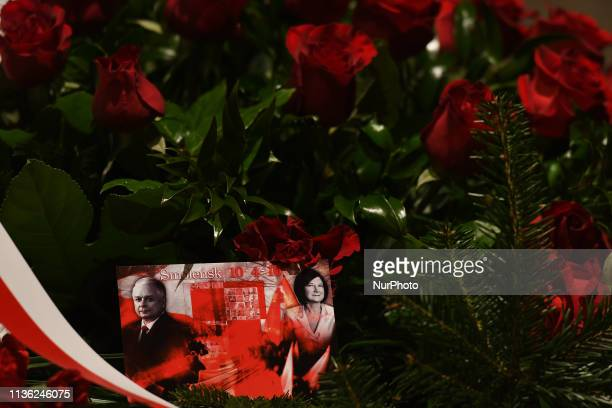 An image of the late Polish President Lech Kaczynski and his wife Maria Kaczynska seen at the top of sarcophagus covered with wreaths containing...