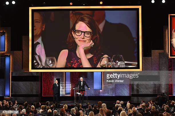 An image of writer Anne Stringfield appears on a video screen as honoree Steve Martin accepts the AFI Life Achievement Award onstage during the 2015...