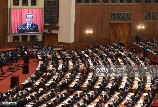 An image of Yu Zhengsheng Chairman of the National Committee of the Chinese People's Political Consultative Conference is seen on a screen past...