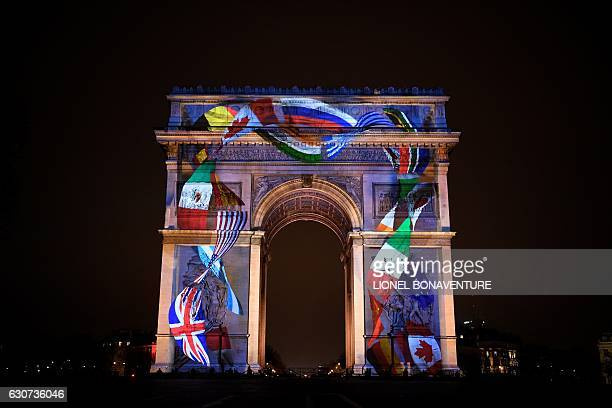 An image showing various countries' flags is projected on the Arc de Triomphe monument during a laser and 3D video mapping show on the theme of the...