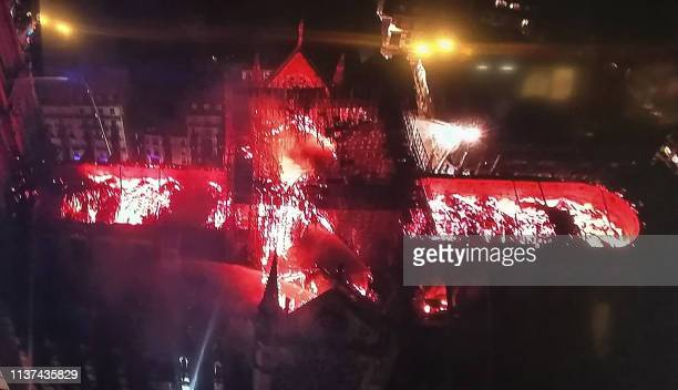 TOPSHOT An image taken from a television screen shows an aerial view of the NotreDame Cathedral engulfed in flames on April 15 in the French capital...
