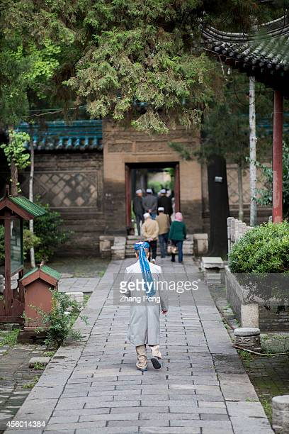 XI'AN SHAANXI CHINA An Imam and Moslem men are walking out of the Xi'an Great Mosque after worship Xi'an great Mosque is a blend of traditional...