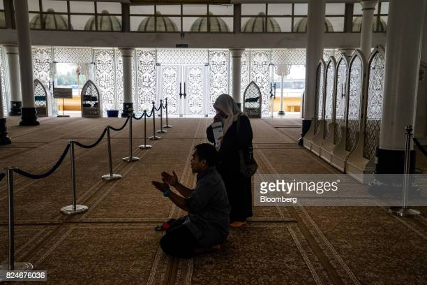 An imam explains the process of prayer to a visitor at the Crystal Mosque in Kuala Terengganu Terengganu Malaysia on Monday July 23 2017 With a...