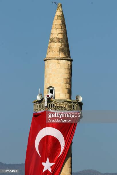 An Imam hangs a Turkish flag to a mosque's minaret near Syrian border in Kirikhan district of Turkey's Hatay in support of 'Operation Olive Branch'...