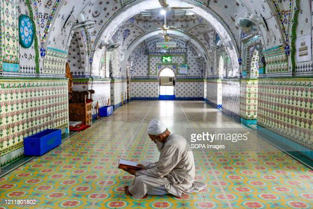 An Imam is seen sitting inside the mosque while reading the holy Qur'an during the holy month of Ramadan. Ramadan is the Islamic calendar's holistic...