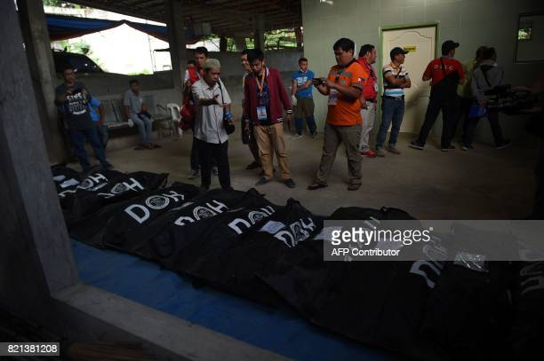 An imam sprinkles water as he prays in front of body bags containing the remains of victims of Marawi siege prior to a mass burial at a funeral...