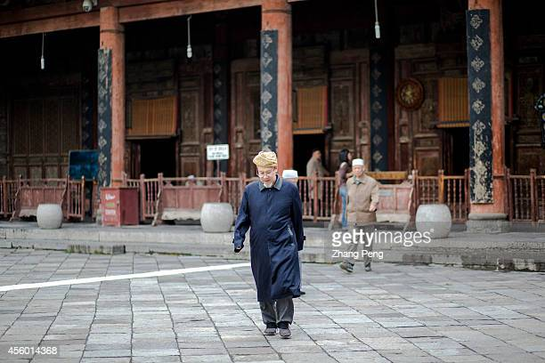 XI'AN SHAANXI CHINA An imam walks out of the main hall for worship at the Xi'an Great Mosque The hall can hold 1000 believers to do their religious...