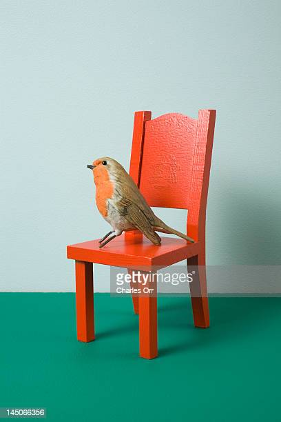 An imitation bird sitting on a miniature chair