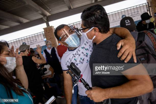 An immigrant, , and volunteers embrace after a group of at least 25 asylum seekers were officially allowed to cross from a migrant camp in Mexico...