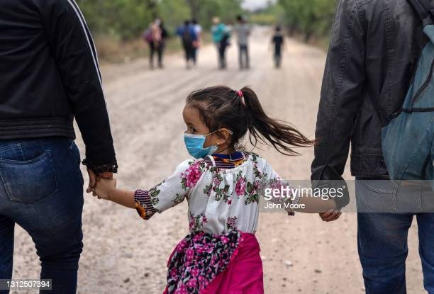 An immigrant child glances back towards Mexico after crossing the border into the United States on April 14, 2021 in La Joya, Texas. Many Central...