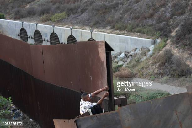 An immigrant climbs over the USMexico border fence on December 4 2018 from Tijuana Mexico Many immigrants making the crossing plan to request...