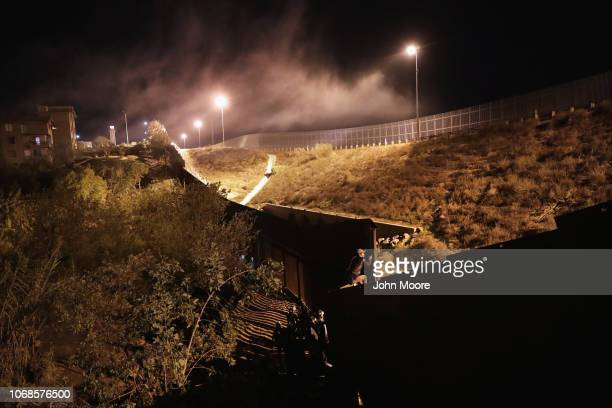 An immigrant climbs over the USMexico border fence on December 4 2018 into San Diego from Tijuana Mexico Many immigrants making the crossing plan to...