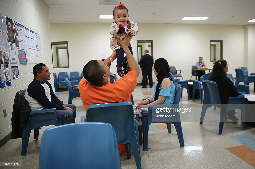 An immigrant detainee holds his daughter during a family visitation visit at the Adelanto Detention Facility on November 15, 2013 in Adelanto, California. The facility, the largest and newest Immigration and Customs Enforcement (ICE), detention center in California, houses an average of 1,100 immigrants in custody pending a decision in their immigration cases or awaiting deportation. The average stay for a detainee is 29 days. The facility is managed by the private GEO Group. ICE detains an average of 33,000 undocumented immigrants in more than 400 facilities nationwide.