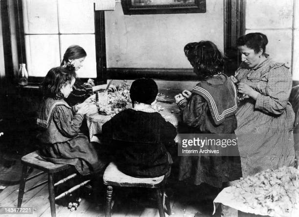 An immigrant family gathers together to produce floral necklaces New York January 1908 The Leveroni family at 122 Sullivan Street earn 4 cents a...