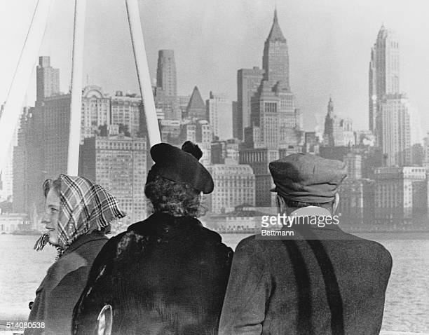 An immigrant family looks out over the New York skyline as they arrive in the USA from Germany aboard the SS Nieuw Amsterdam