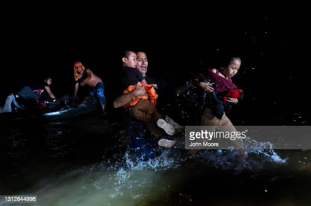 An immigrant father grips his children while walking ashore on the bank of the Rio Grande at the U.S.-Mexico border on April 14, 2021 in Roma, Texas....