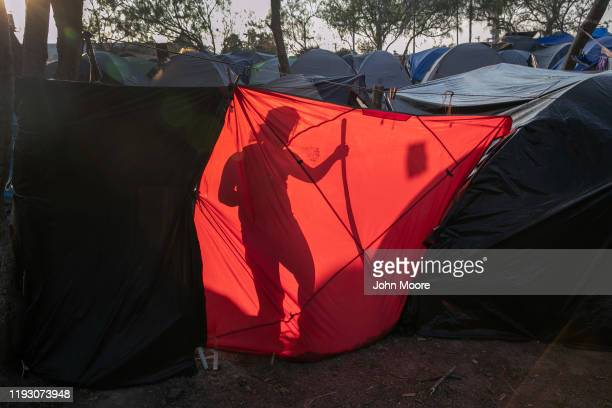 An immigrant from Honduras cleans up her family's living area at a camp for asylum seekers on December 08 2019 in the border town of Matamoros Mexico...