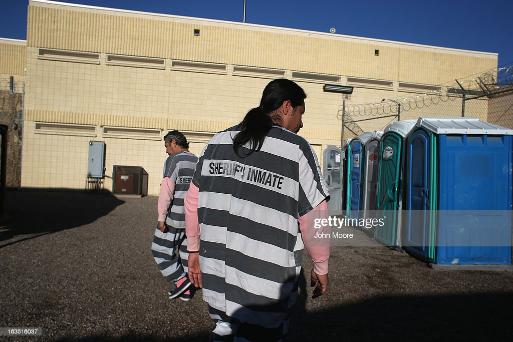 An immigrant inmate walks to the bathroom at the Maricopa County Tent City jail on March 11, 2013 in Phoenix, Arizona. The striped uniforms and pink undergarments are standard issue at the facility. The tent jail, run by Maricopa County Sheriff Joe Arpaio, houses undocumented immigrants who are serving up to one year after being convicted of crime in the county. Although many of immigrants have lived in the U.S for years, often with families, most will be deported to Mexico after serving their sentences.