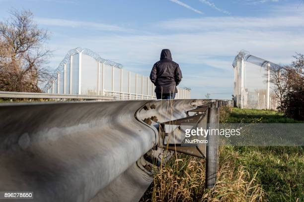 An immigrant is walking on a road towards fences which surround border zone in Calais France on December 19 2017