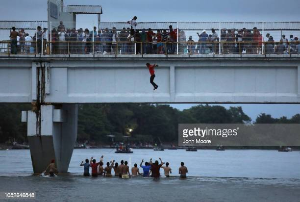 An immigrant jumps off a bridge to enter Mexico from the border with Guatemala as part of the immigrant caravan on October 20 2018 in Ciudad Hidalgo...