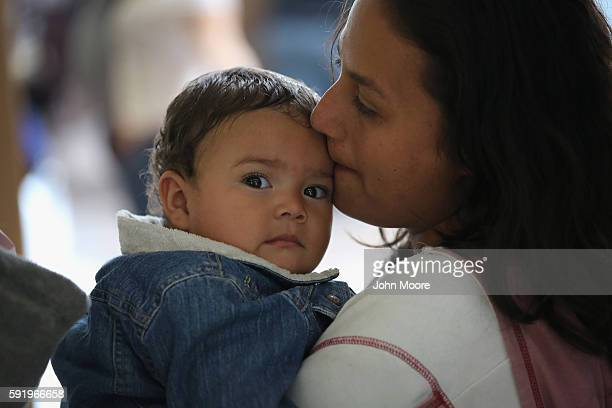 An immigrant mother and child from Honduras wait to take a bus to Florida on August 19 2016 from McAllen Texas After crossing the Rio Grande from...