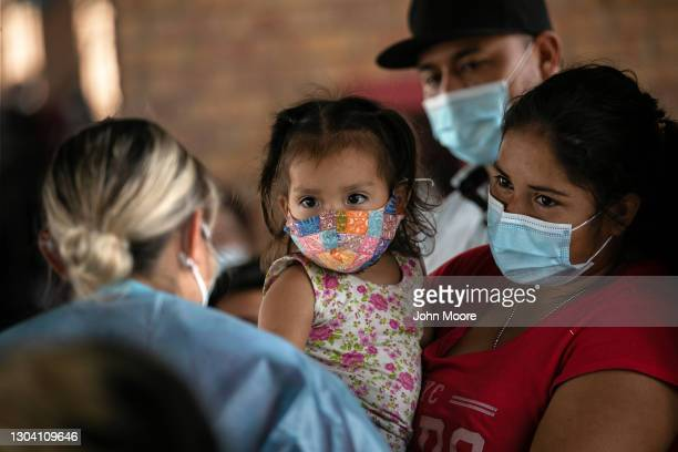 An immigrant mother holds her daughter while awaiting Covid-19 test results on February 25, 2021 after being released by U.S. Immigration authorities...