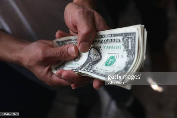 An immigrant prepares to change his $15 into Guatemalan Quetzales after he arrived on an ICE deportation flight on February 9 2017 to Guatemala City...
