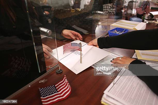 An immigrant receives a naturalization certificate and an American flag before taking the oath of allegiance to the United States at the district...
