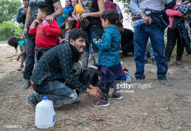 An immigrant removes a child's shoelaces as per US Border Patrol protocol after they were taken into custody by federal agents on July 02 2019 in Los...