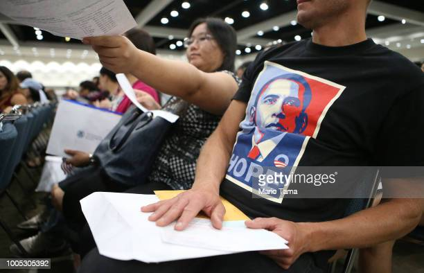 An immigrant wears a Barack Obama shirt as another hands in a voter registration form during a naturalization ceremony on July 25 2018 in Los Angeles...