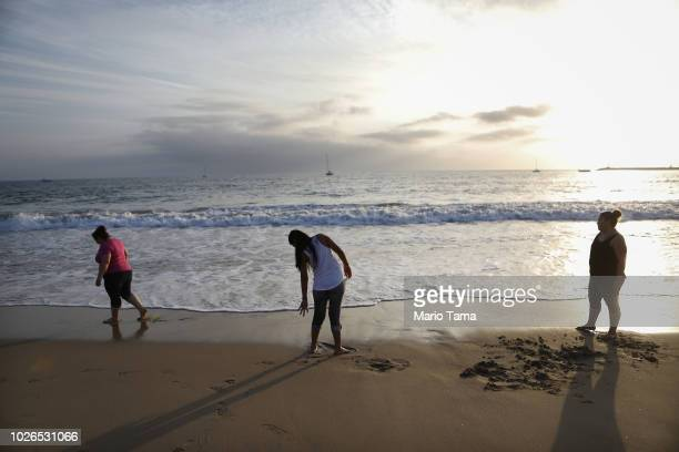 An immigrant who identified herself only as Vioney recently released after spending six months in an ICE detention facility walks on the beach with...