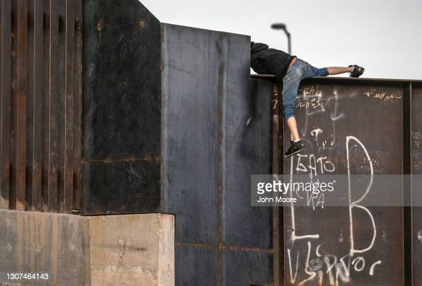An immigrant, who said he was a 16-year old from Mexico, climbs over the border wall after crossing the Rio Grande into the United States on March...