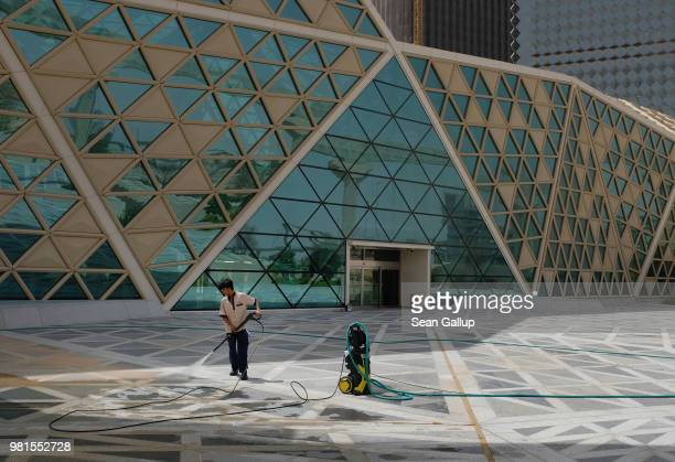 An immigrant worker cleans a plaza from sand with a hose at the newlybuilt King Abdullah Financial District on June 20 2018 in Riyadh Saudi Arabia...
