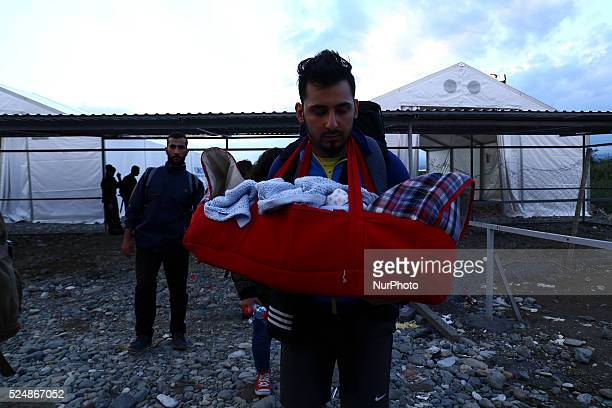 An immigrants that just entered Macedonia is carrying his baby while he is entering in Gevgelija the train that will transport them to the border...