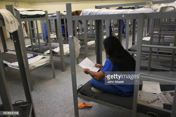 An immigration detainee from Bangladesh reads through his case papers while on his bunk at the Immigration and Customs Enforcement detention facility...