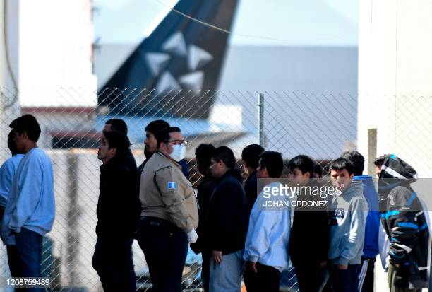An immigration official uses a protective face mask as a preventive measure against the new coronavirus, COVID-19, upon the arrival of Guatemalan...