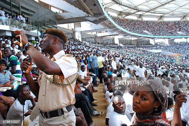 An immigration security agent speaks on a microphone to jobseekers gathered in Abuja National Stadium to apply for work at the Nigerian immigration...